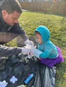 Picture of dad and daughter doing tie-dye outside. Part of a spring kids activities blog series.